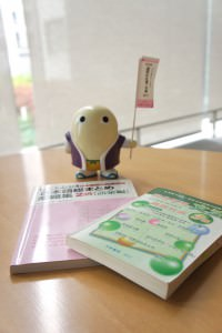 Mayumaro, one of Kyoto Prefecture's cute mascots (he's a silkworm cocoon!) stands guard over some of Rae's study materials.